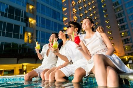 Twee jonge en knappe Aziatische Chinese koppels of vrienden drinken cocktails in een luxe en chique bar van het hotel zwembad