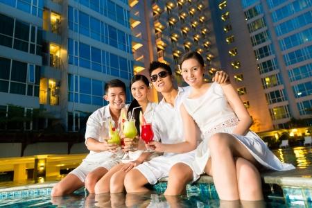 personas festejando: Dos parejas chinas asiáticas jóvenes y guapos o amigos bebiendo cócteles en un lujoso y elegante bar de la piscina del hotel