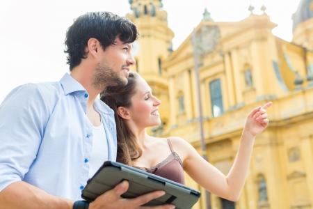 Mann und Frau oder junge Paare, die Reise als Touristen in M�nchen an der Odeon Kirche mit Stadtkarte auf dem Tablet-Computer f�r die Navigation Lizenzfreie Bilder