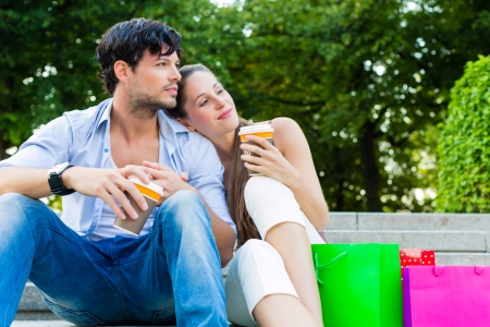 Man and woman or young couple drinking coffee and sitting in city park in summer with shopping bags photo