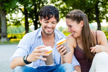 huddling: Man and woman or young couple drinking coffee and sitting in city park in summer on stairs