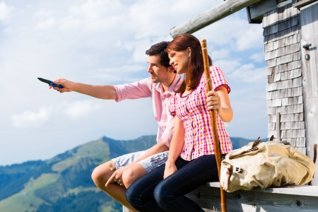 Hiking - Young couple sitting at mountain hut in the Bavarian Alps and enjoys the panorama in the leisure time or in vacation photo