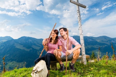 Hiking - Young couple sitting on mountain summit at cross in the Bavarian Alps and enjoys the panorama in the leisure time or in vacation photo