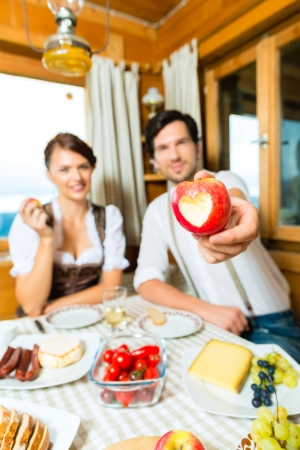 Couple in a traditional mountain hut having a meal, breakfasting with fruits, cold cuts, cheese and bread Stock Photo