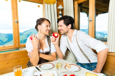 breakfasting: Couple in a traditional mountain hut having a meal, breakfasting with fruits, cold cuts, cheese and bread Stock Photo