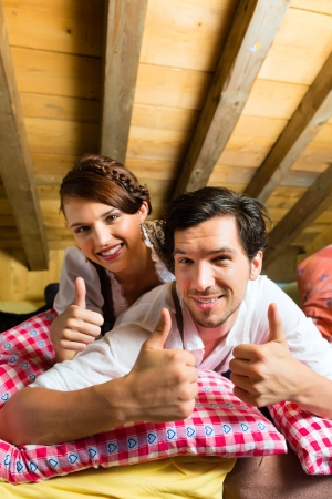 trachten: Young couple in bed on the floor of a barn or a mountain hut in the Alps enjoying the leisure time