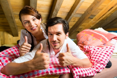 tracht: Young couple in bed on the floor of a barn or a mountain hut in the Alps enjoying the leisure time