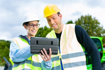 the grater: Construction worker and engineer on site discussing blueprints on pad or tablet computer, excavator and other construction machinery in background
