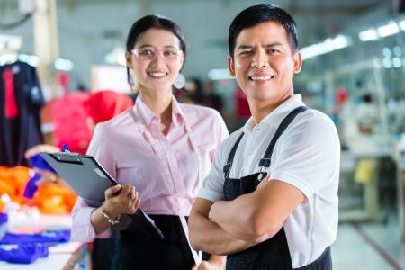 supervisores: Trabajador indonesio o capataz y modista o diseñador que mira en el sujetapapeles en una fábrica asiática para la ropa