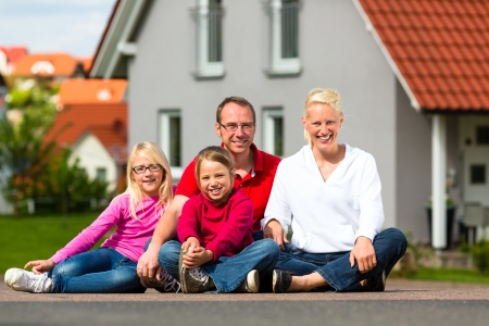 Young family sitting in the sun in front of their new home and laughing photo