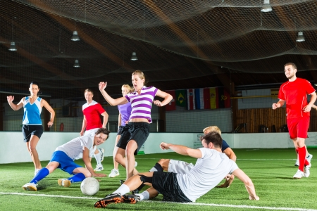 women playing soccer: Men and women in mixed sport team playing football or soccer indoor and trying to score goal