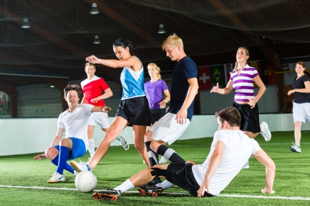 indoors: Men and women in mixed sport team playing football or soccer indoor and trying to score goal