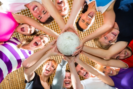 Men and women in mixed sport team playing football or soccer indoor and presenting team spirit Stock Photo
