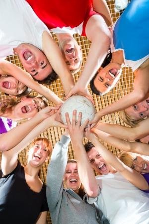 Mannen en vrouwen in gemengde sport team spelen voetbal of voetbal indoor en presenteren teamgeest