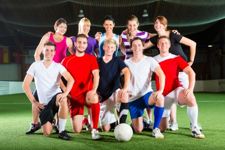 women playing soccer: Men and women in mixed sport team playing football or soccer indoor