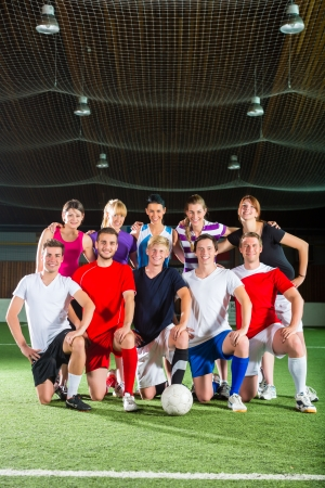 Men and women in mixed sport team playing football or soccer indoor photo