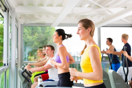 Running on treadmill in gym or fitness club - group of women and men exercising to gain more fitness photo