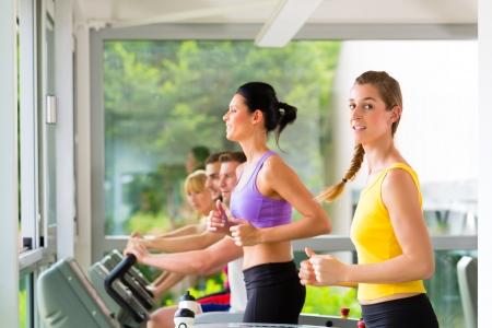 Que se ejecutan en la caminadora en gimnasio o fitness club - grupo de mujeres y hombres ejercicio para ganar más aptitud