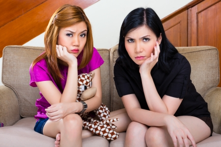 tedious: Two Indonesian Asian girl friends are bored or sad and looking in the camera