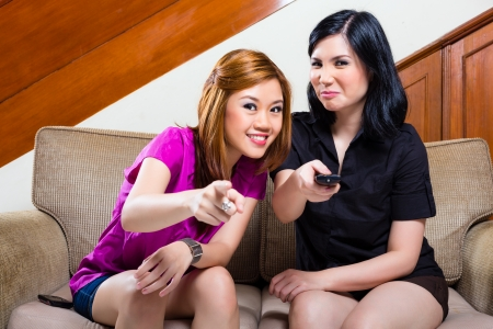 Two Indonesian girl friends watching a movie and change the TV program with the remote control photo