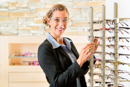 Young woman at optician with glasses, she might be customer or salesperson Stock Photo