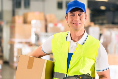 Warehouseman with protective vest and scanner, holds package, he standing at warehouse of freight forwarding company Stock Photo