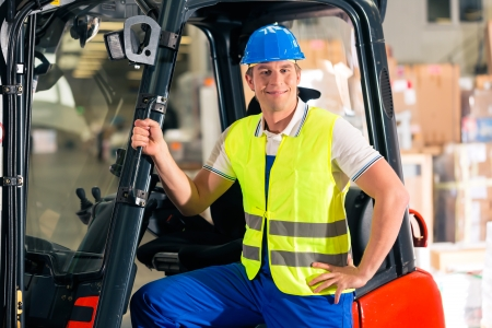 forklift driver in protective vest and forklift standing at warehouse of freight forwarding company, smiling photo