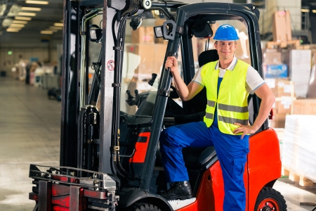 forklift driver: forklift driver in protective vest and forklift standing at warehouse of freight forwarding company, smiling