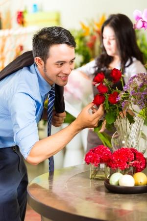 generoso: Hombre asiático o indonesio joven se interesa por un Ramo de Rosas Foto de archivo