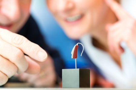 Older donna o pensionato femmina con problemi di udito fare un test dell'udito, in primo piano è un modello di un apparecchio acustico Archivio Fotografico - 25003695