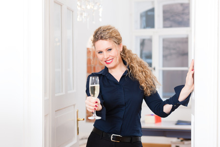 Young business woman at home, drinking sparkling wine in a glass and takes a break at after hour photo