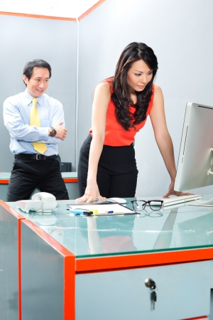 Asian Employee or secretary getting being sexually harassed by her boss or manager, he is looking her at the backside while she is working  Stock Photo