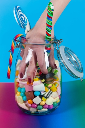 goodies: Young woman with many unhealthy sweets or candy in Studio, she have a sweet tooth and grabbing some goodies out of a glass
