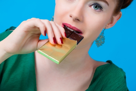 sweet tooth: Young woman with chocolate in Studio, she have a sweet tooth and biting in a chocolate bar out of a glass