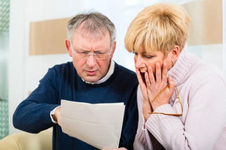 Two elderly people have received a letter, maybe it's a reminder or a Bill, but most likely it is the tax assessment notice Stock Photo - 25003675
