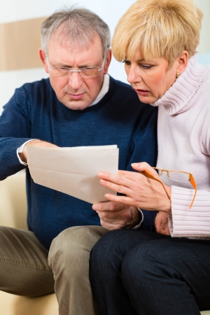 inform: Two elderly people have received a letter, maybe its a reminder or a Bill, but most likely it is the tax assessment notice