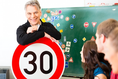 Driving school - driving instructor and student drivers look at a tempo thirty Road sign, in the background are traffic signs Banco de Imagens