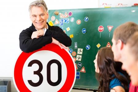Rijschool - rij-instructeur en leerling chauffeurs kijken naar een tempo dertig Verkeersbord, op de achtergrond zijn verkeersborden
