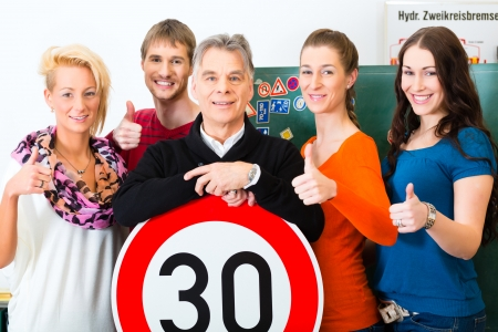 Driving school - driving instructor and student drivers look at a tempo thirty Road sign, in the background are traffic signs Stok Fotoğraf