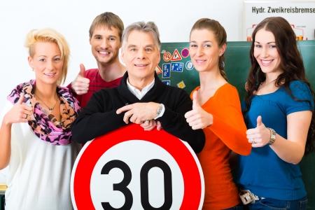 Rijschool - rij-instructeur en leerling chauffeurs kijken naar een tempo dertig Verkeersbord, op de achtergrond zijn verkeersborden Stockfoto
