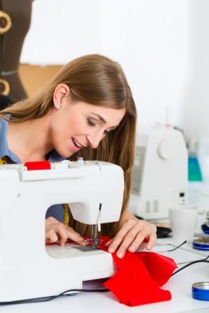 freiberufler: Freelancer - Fashion Designer oder Schneider arbeitet an einem Design oder Entwurf, n�ht sie mit einer N�hmaschine