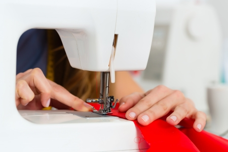Freelancer - Fashion designer or Tailor working on a design or draft, she sews with a sewing machine Stock Photo