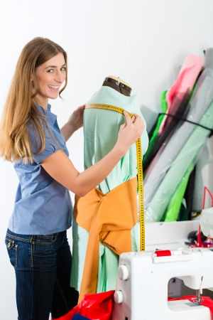 tailor measure: Freelancer - Fashion designer or Tailor working on a design or draft, she takes measure on a dressmakers dummy