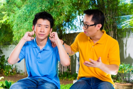 annoyed: Chinese Asian father talking to his son but he will not listening, holding his ears with his hands refusing the good advice