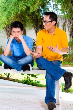 Chinese Asian father talking to his son but will not listening, refusing the good advice Stock Photo