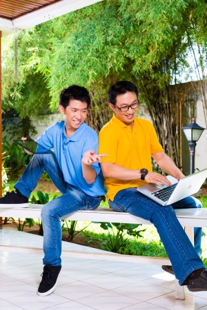 Chinese father talking with his son, they enjoying the leisure time together with a tablet computer and laptop photo