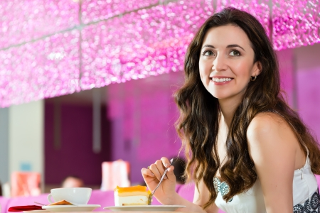 Young woman in a cafe or ice cream parlor eating a cake, maybe she is single or waiting for someone Stock Photo - 25003663