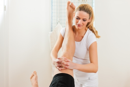 physical therapist: Patient at the physiotherapy doing physical therapy exercises with his therapist