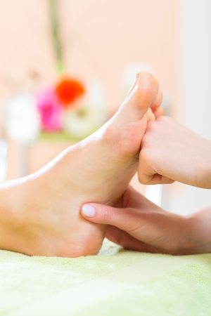 foot massage: Woman in a nail salon receiving a pedicure by a beautician, she is getting a foot massage Stock Photo