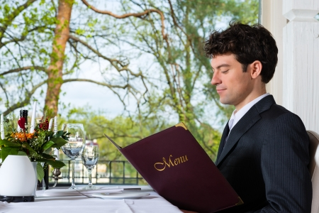 Man or Businesspeople having business lunch in a fine dining restaurant and choose in the menu photo
